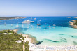 Aerial view of an emerald and transparent mediterranean sea with a white beach and some yachts. Gulf of the Great Pevero, Costa Smeralda, Sardinia, Italy.