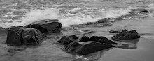 Large Rocks On Beach With Waves And Splash