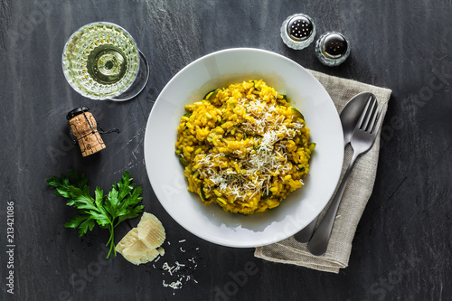Photo  Italian dish yellow Risotto milanese with saffron, zucchini and Parmesan cheese on a black slate table with white wine in a glass