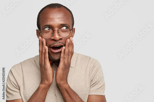 Headshot of emotive amazed dark skinned male touches cheeks and looks with wonderment aside, notices beautiful woman, says: Wow, it`s cool! African American man rejoices something, isolated on white