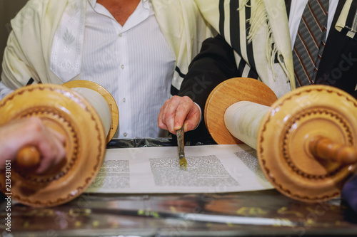 A praying man with a tefillin on his arm and head, holding a Torah, while reading a pray at a Jewish ritual Bar Mitzvah ceremony .
