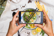 Smartphone Food Photography. Woman Hands Take Phone Photo. Ramen Noodle Soup With Egg, Corn And Meat In Bowl. Asian Thai Traditional Authentic Food With Vegetables Served In Cafe Or Restaurant