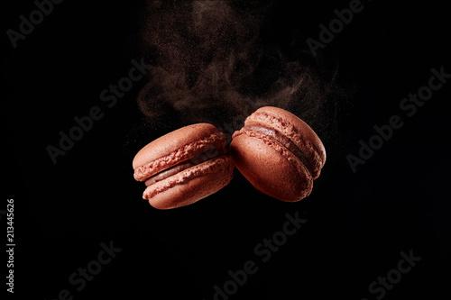 Aluminium Prints Macarons Macaron explosion. French chocolate macaron with cocoa powder against black background