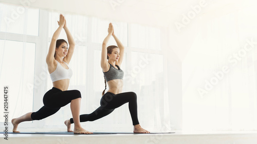 Obraz Two sporty women practice yoga in light gym - fototapety do salonu