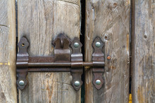 Close-up Of Lit By Sun Old Rough Made Of Wooden Planks House Door Or Barn Gate With Iron Rusty Slide Bolt Lock. Outdated Technology, Safety, Security And Protection From Thieves Concept.