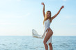 Beautiful happy young woman in a white summer satin dress stands at sea background