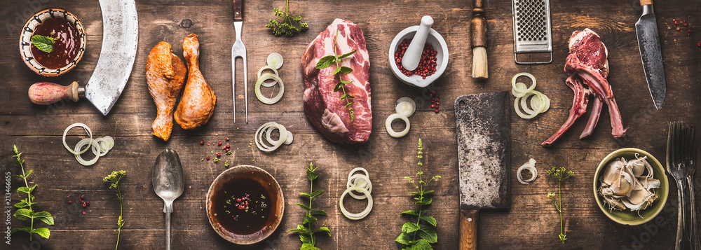 Fototapety, obrazy: Flat lay of various grill and bbq meat : chicken legs, steaks, lamb ribs with vintage kitchenware kitchen utensils:  Meat Fork and Butcher Cleaver and herbs knife. Sauces and ingredients for grilling,
