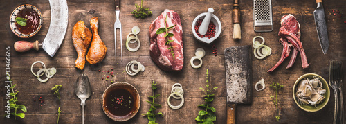 Flat lay of various grill and bbq meat : chicken legs, steaks, lamb ribs with vintage kitchenware kitchen utensils:  Meat Fork and Butcher Cleaver and herbs knife. Sauces and ingredients for grilling, - 213466655