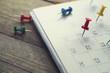 Leinwandbild Motiv close up of pin on calendar planning for business meeting or travel planning concept