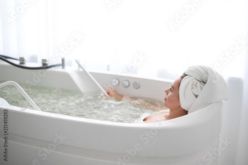 Valokuvatapetti Side view serene girl lying in cozy bath in cosmetology center