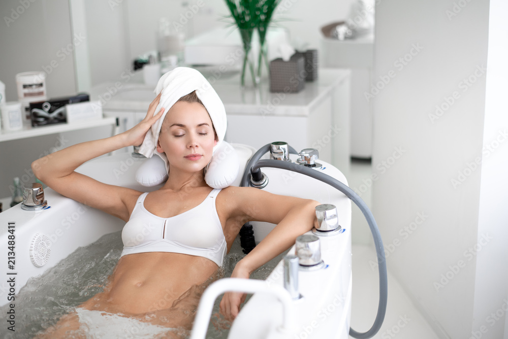 Fototapeta Portrait of pensive female with closing eyes locating in comfortable bath in spa salon
