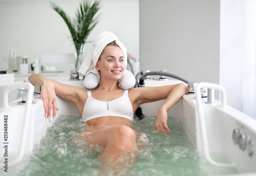 Fototapeta Portrait of laughing young lady resting in spa salon. She leaning on bath