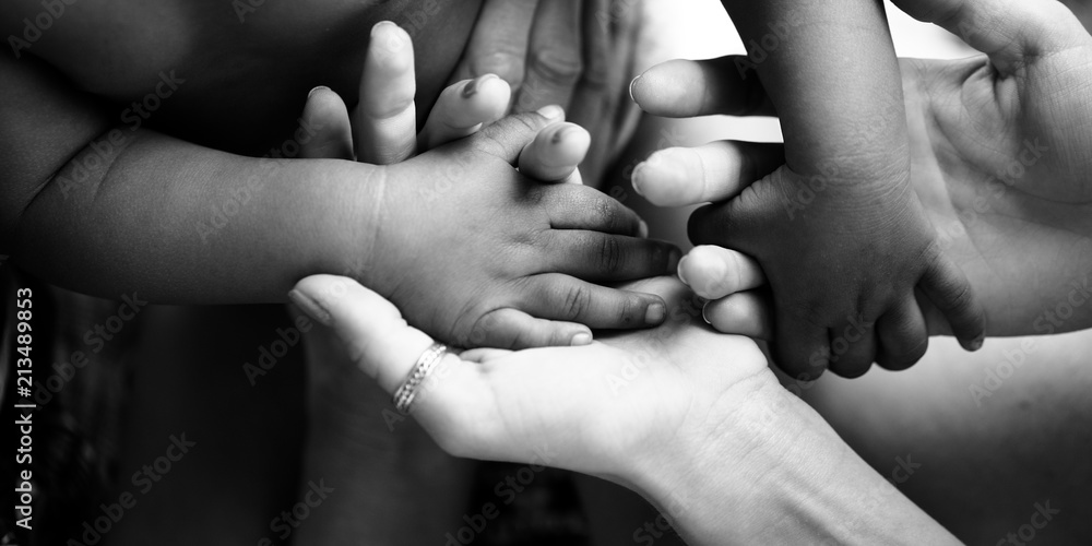 Fototapeta Touching moment, touch of the hand of a small child and an adult woman. Mother and child, adoptive children, adoption. A white woman and a dark skinned child. Interracial relations, multiracial family