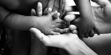 Touching Moment, Touch Of The Hand Of A Small Child And An Adult Woman. Mother And Child, Adoptive Children, Adoption. A White Woman And A Dark Skinned Child. Interracial Relations, Multiracial Family