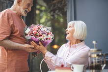 Wow. Side View Profile Of Happy Senior Man Giving Flowers To Old Lady Sitting At Table In Cafe.  They Are Joyful And Pleased To Have Date Together