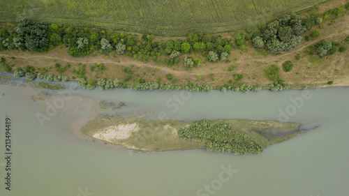Fotobehang Khaki Aerial top view of summer green trees, river, roads in forest background. Drone photography. Coniferous and deciduous trees, forest road. Beautiful panoramic photo over the tops of pine forest.