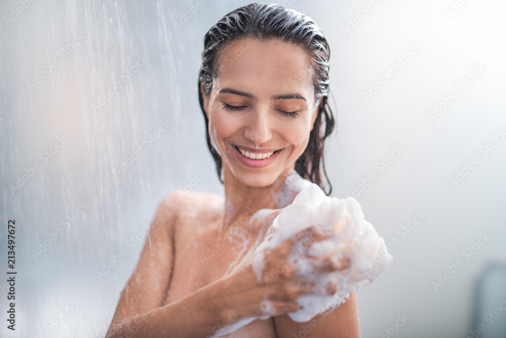 Fototapeta Portrait of happy girl taking shower with gel. She washing with puff