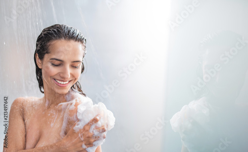 Fotografia Portrait of beaming woman rubbing body with foam while standing under steam of water