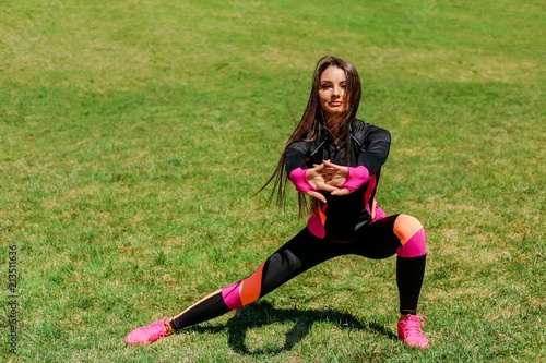 Sporty girl doing outdoor exercises in the Park on the lawn Wallpaper Mural