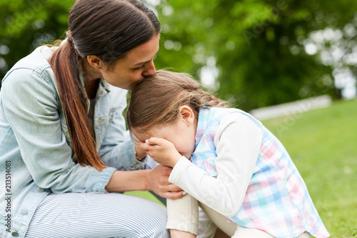Young woman kissing her crying daughter on head, embracing and comforting her du Canvas Print