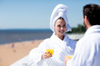Young woman in white bathrobe and towel having juice and talking to her husband during honeymoon vacation at summer resort