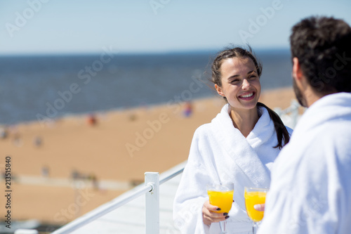 Cherful young wife with glass of juice looking at husband while talking to him at spa resort on sunny day