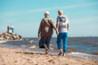 Back view of affectionate senior couple holding by hands while walking down sandy beach along coastline