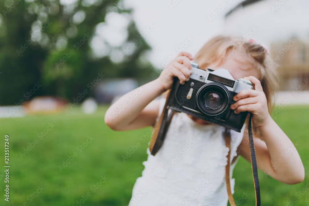 Fototapety, obrazy: Little cute child baby girl in light dress take picture on retro vintage photo camera on green grass in park. Mother, little kid daughter. Mother's Day, love family, parenthood, childhood concept.