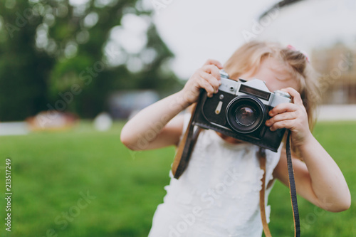 Little cute child baby girl in light dress take picture on retro vintage photo camera on green grass in park. Mother, little kid daughter. Mother's Day, love family, parenthood, childhood concept.