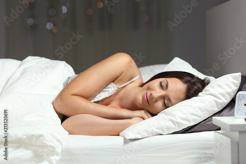 Obraz Happy woman sleeping on the bed in the night - fototapety do salonu