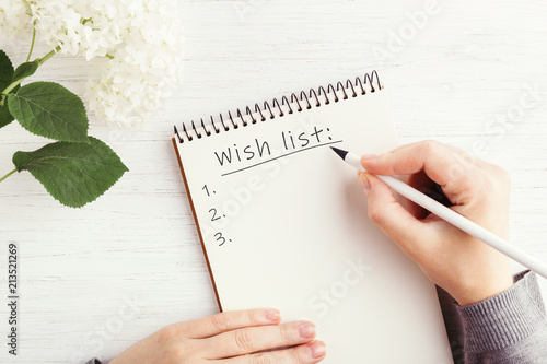 Woman's hand writing Wish list in notebook on white wooden table Poster Mural XXL