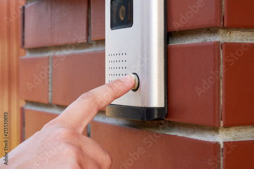 Fényképezés The female hand presses a button doorbell with intercom