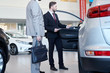 Car salesman representing new car to male customer at auto showroom