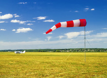 Red And White Windsock Wind Sock On Blue Sky On The Aerodrome, Yellow Field And Clouds Background