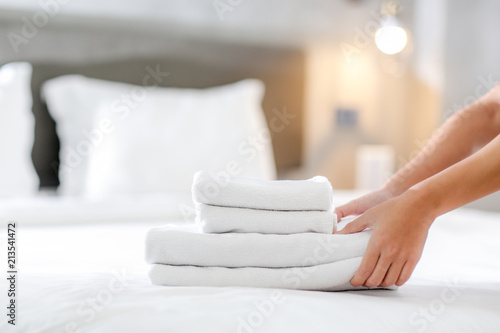 Close-up of hands putting stack of fresh white bath towels on the bed sheet Canvas-taulu