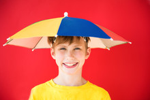 Positive Baby Boy Under Colorful Umbrella On Bright Red Background. The Concept Of Protection And Forecasting