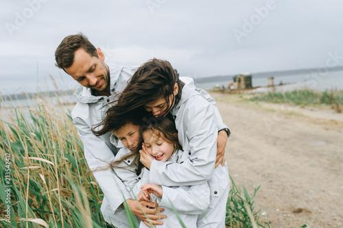 Fotografia  Beautiful family portrait dressed in raincoat near the lake