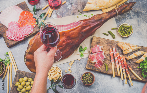 Poster Sushi bar Mans hand holding wine glass frome above table with spanit or italian appetizers, whole leg of ham serrano and red an rose wine