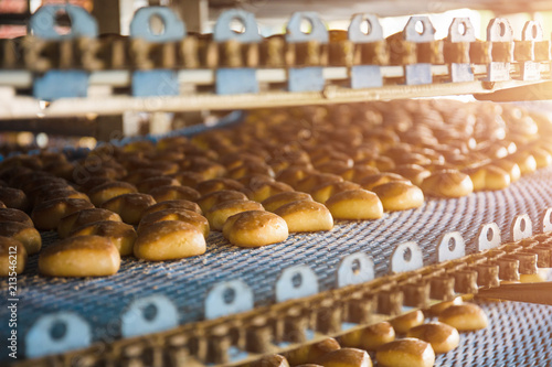 Cuadros en Lienzo Cakes on automatic conveyor belt or line, process of baking in confectionery culinary factory or plant