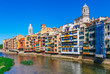 Colorful red, orange and yellow houses and bridge through river Onyar in Girona, Catalonia, Spain. Scenic ancient town. Famous tourist resort destination perfect place for holiday and vacation