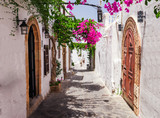 Fototapeta Uliczki - Narrow street in Lindos town on Rhodes island, Dodecanese, Greece. Beautiful scenic old ancient white houses with flowers. Famous tourist destination in South Europe