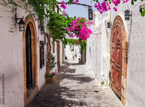 Photo sur Toile Europe Centrale Narrow street in Lindos town on Rhodes island, Dodecanese, Greece. Beautiful scenic old ancient white houses with flowers. Famous tourist destination in South Europe