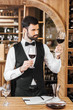 confident young sommelier examining color of wine at wine store