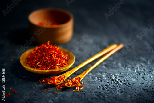 Deurstickers Aromatische Saffron spices. Saffron on black stone table in a wood bowl and a spoon. Spice and herbs on slate background. Cooking ingredients