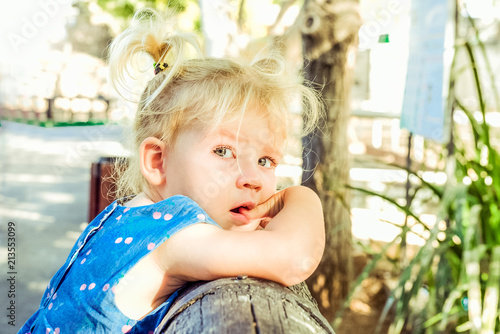 Close up portrait of bondy toddler girl with beautiful blue eyes with tears in the park Canvas Print