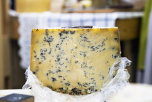 Large Cheese Wheel With Blue Mold On Market Counter, Colorful Colors. Gastronomic Dainty Products On Market Counter, Real Scene In Food Market