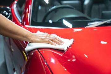 Car detailing - the  holds the microfiber in hand and polishes the car. Selective focus