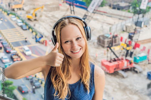 A young woman by the window annoyed by the building works outside, wired soundproof wireless headphones Tablou Canvas