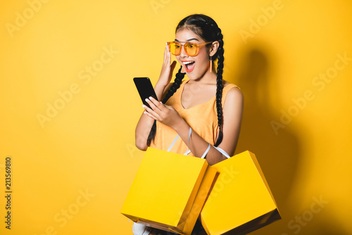 Beautiful young woman with shopping bags using her smart phone on yellow background.Shopaholic shopping Fashion.