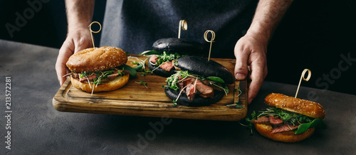 Man holds board different burgers with grilled beef meat
